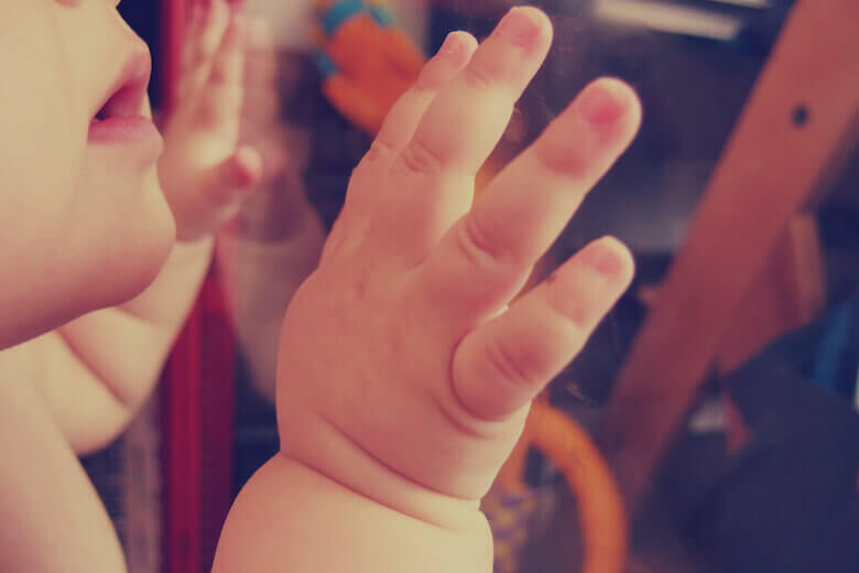 baby looking through glass with baby hands - emergent curriculum article featured image