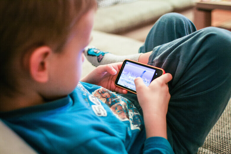 child using phone having screen time - article image for should children use electronics and media