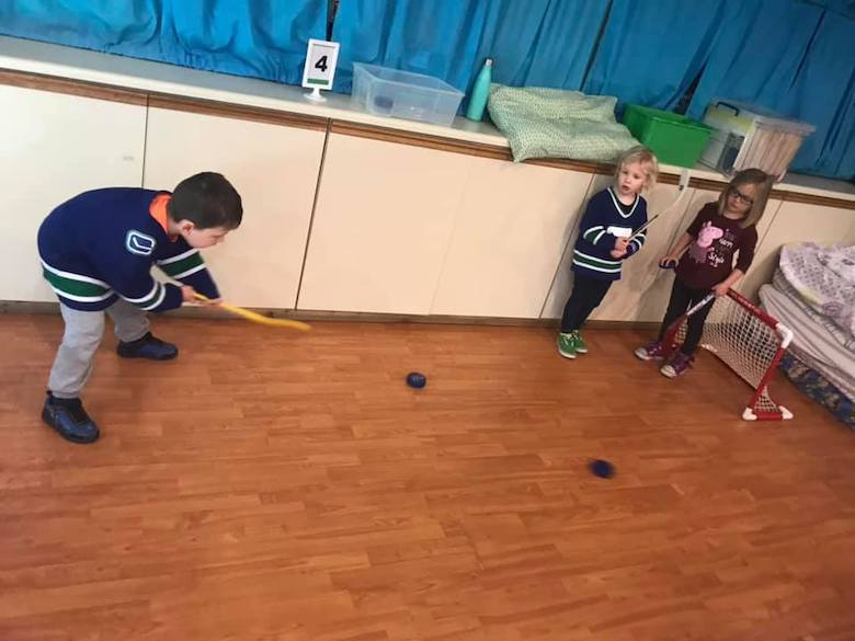 daycare kids playing toy hockey indoors