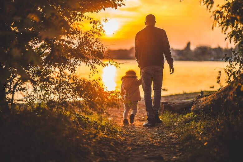 father and child walking - featured image for article on fatherhood involvement in early years