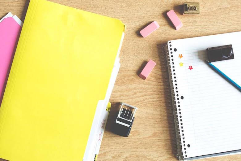 yellow folder with notebook and erasers on desk - image for article on early childhood educational consultant benefits