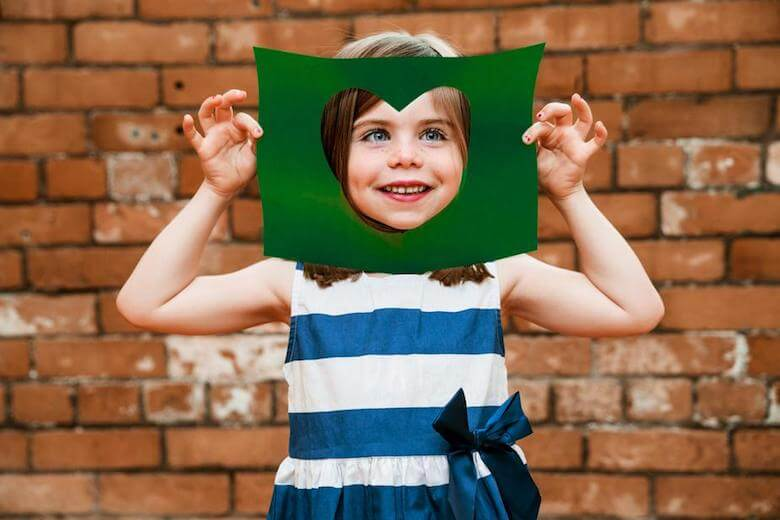 girl holding heart cut out paper - image for article on community service for preschoolers