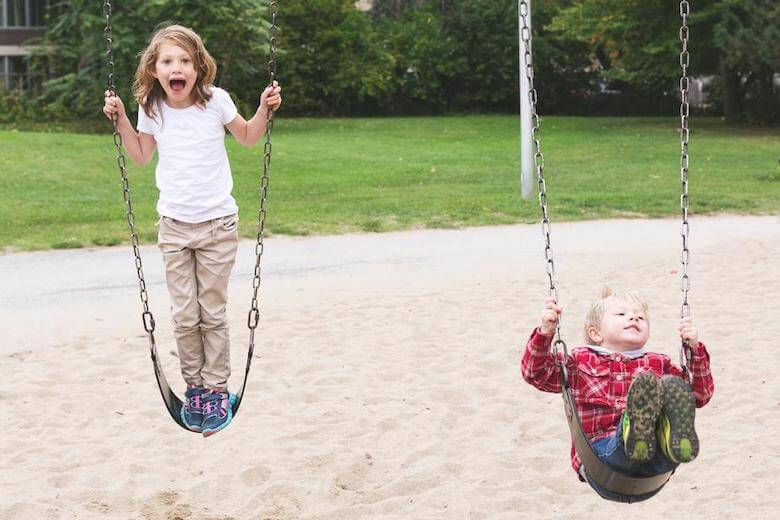 children balancing and pushing on swings depicting gross motor development in childhood
