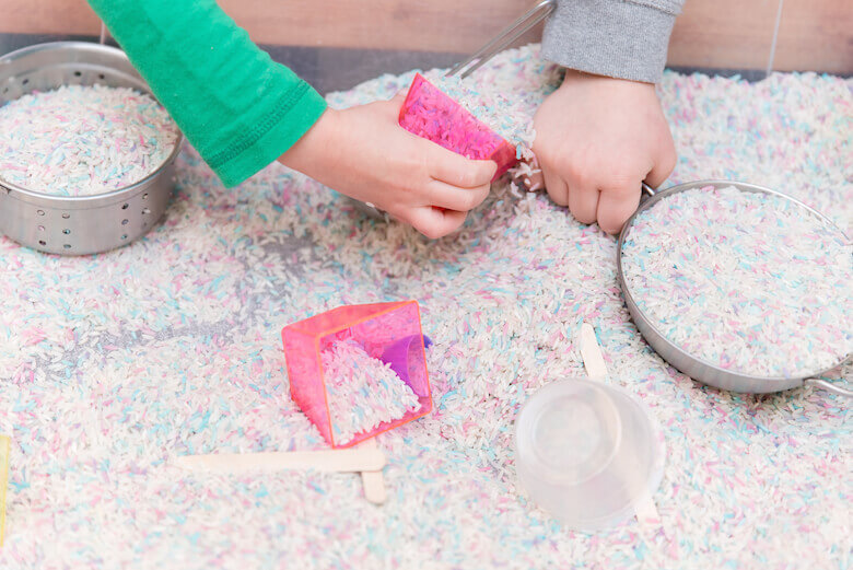 kids hands playing in rice sandbox for sensory development skills at daycare