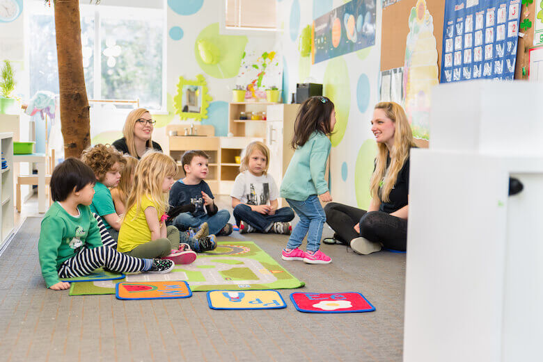 child engaged at daycare with teacher during circle time