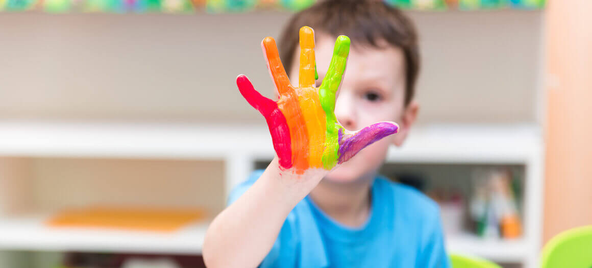 Slider 5: kid with rainbow paint on hands