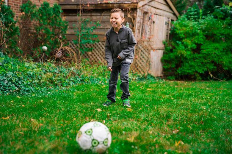 boy playing with soccer ball - image for article on preschool sports ideas