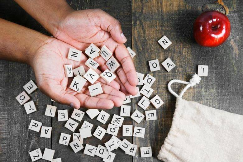scrabble letters in hand with apple - depicting teaching digraphs to preschool children - article image