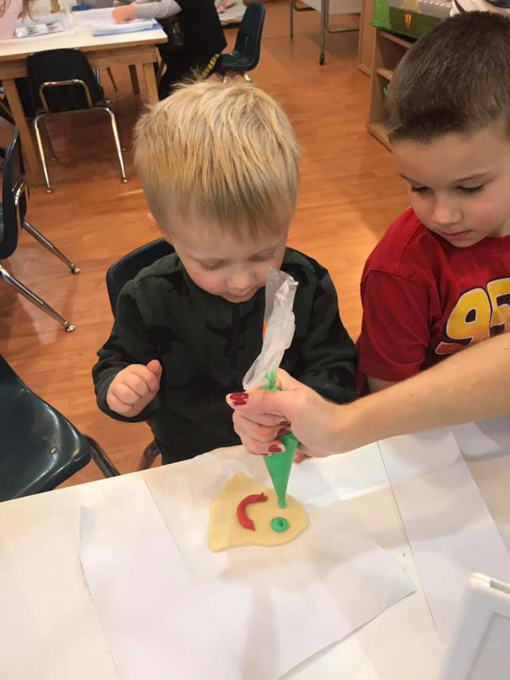 squeezing icing on christmas cookies at preschool